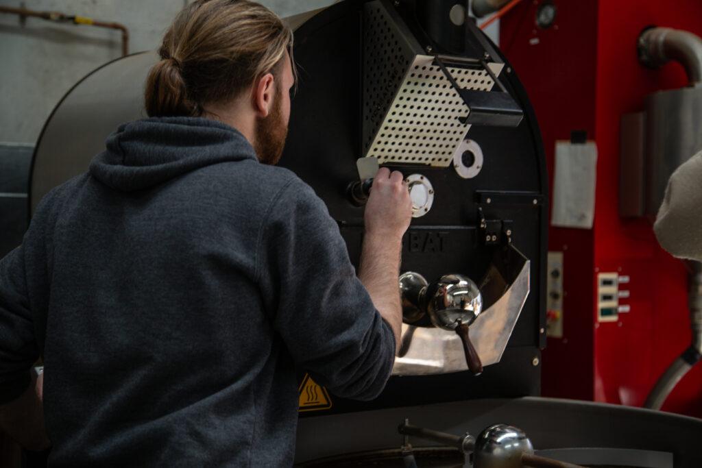 man operating coffee roasting equipment