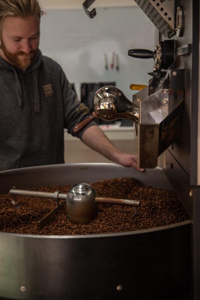 man with beard operating coffee roasting machine